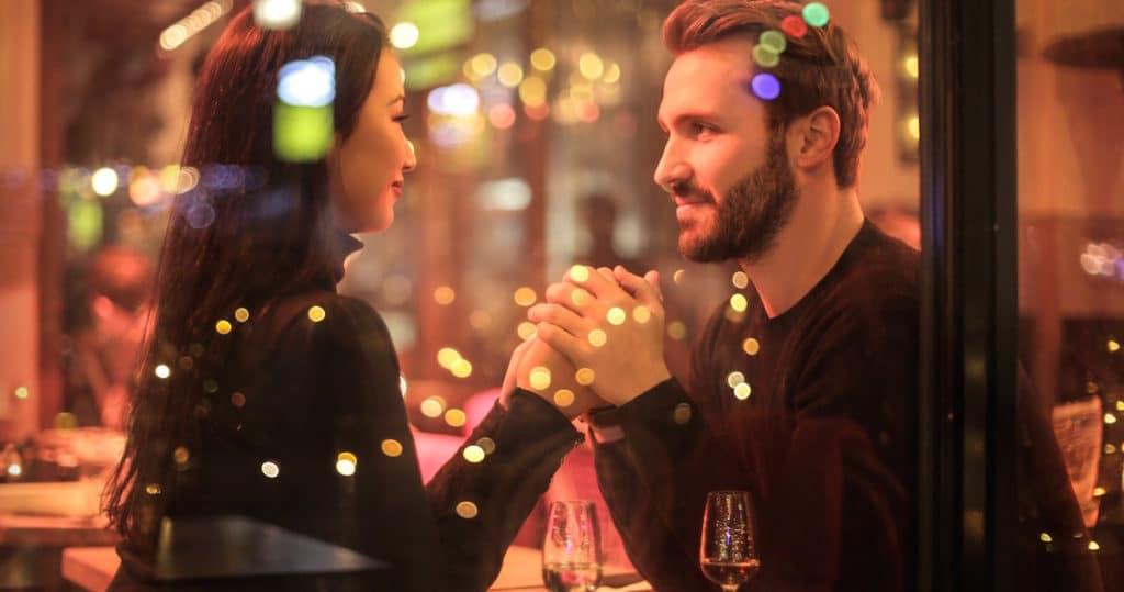 couple se tenant la main au restaurant