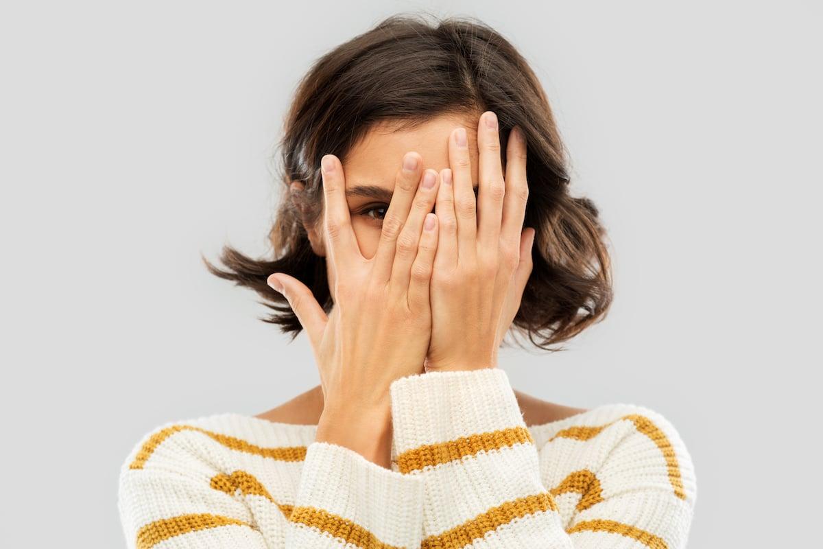 femme timide qui se cache le visage
