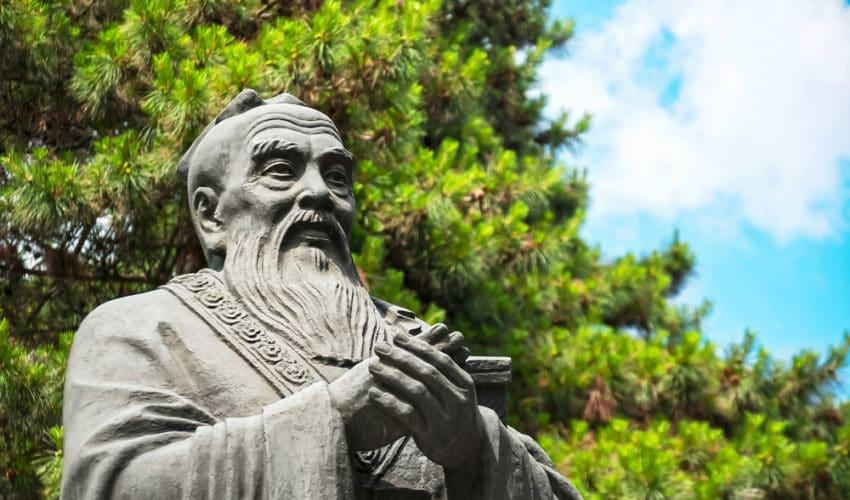 statue de confucius devant un arbre