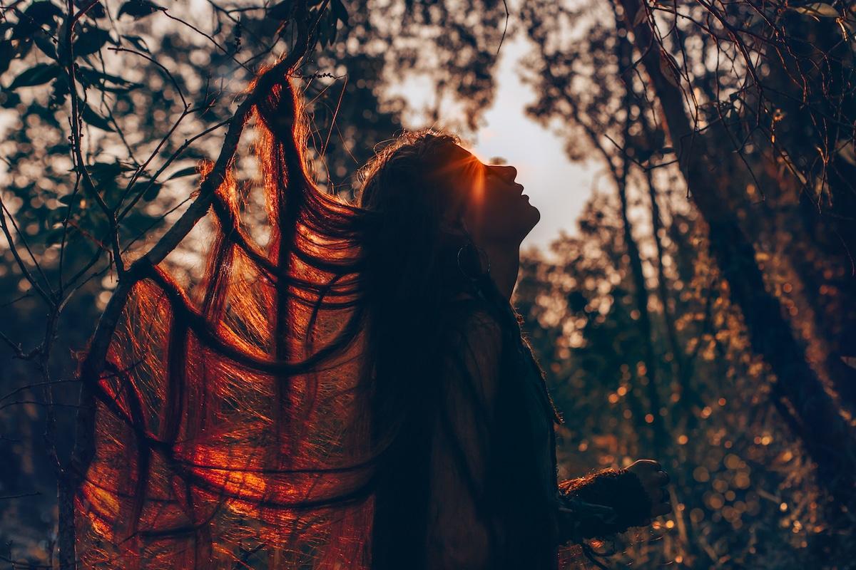 femme dans la foret qui regarde le ciel