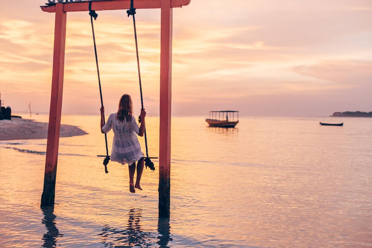 femme sur une balançoire en bord de mer