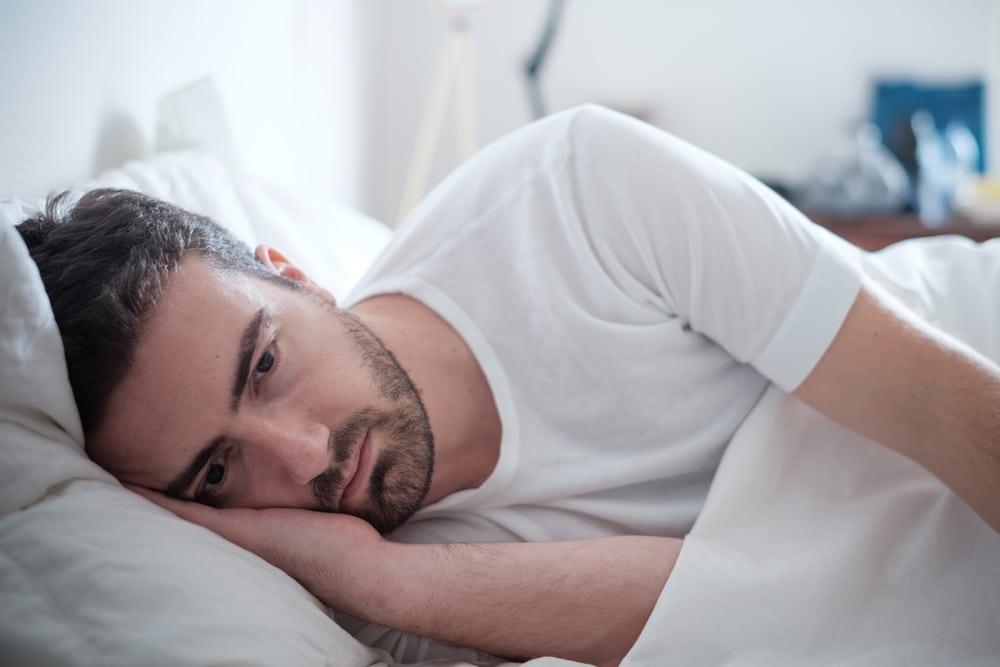 homme qui réfléchie dans son lit
