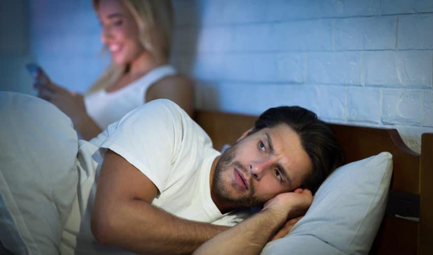 Couple dans un lit, la femme est au téléphone (infidèle ?)
