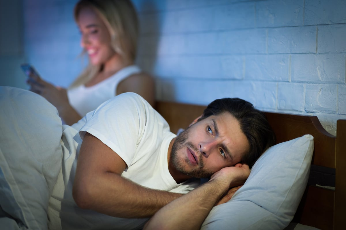 femme qui envoi des sms pendant que son mari dort