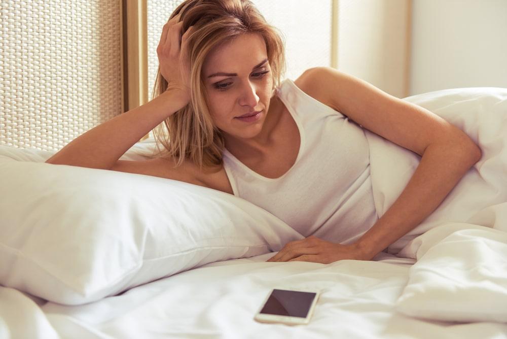 femme qui s'interroge en regardant son téléphone