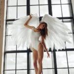 un ange ailé debout devant une fenètre