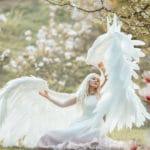un ange ailé assis sur l'herbe