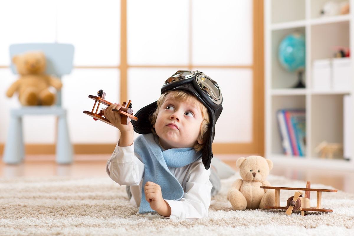 enfant qui joue avec un avion en bois