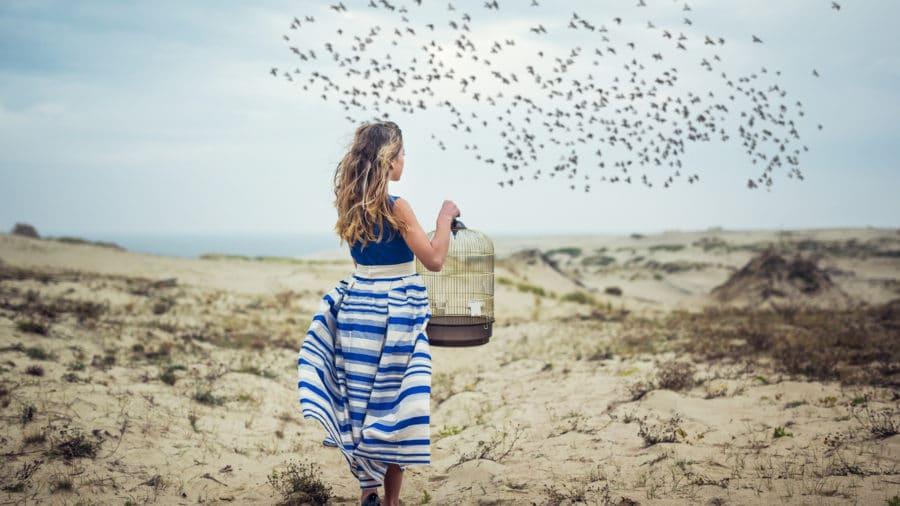 femme libérant des oiseaux de leur cage