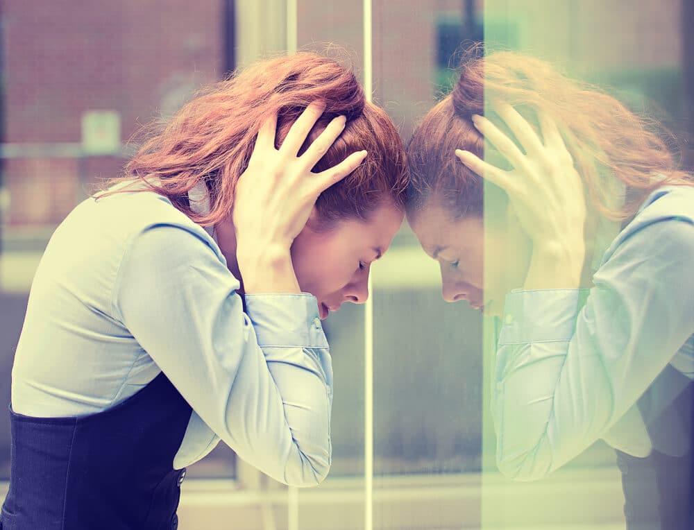 femme qui pose son front contre un mur