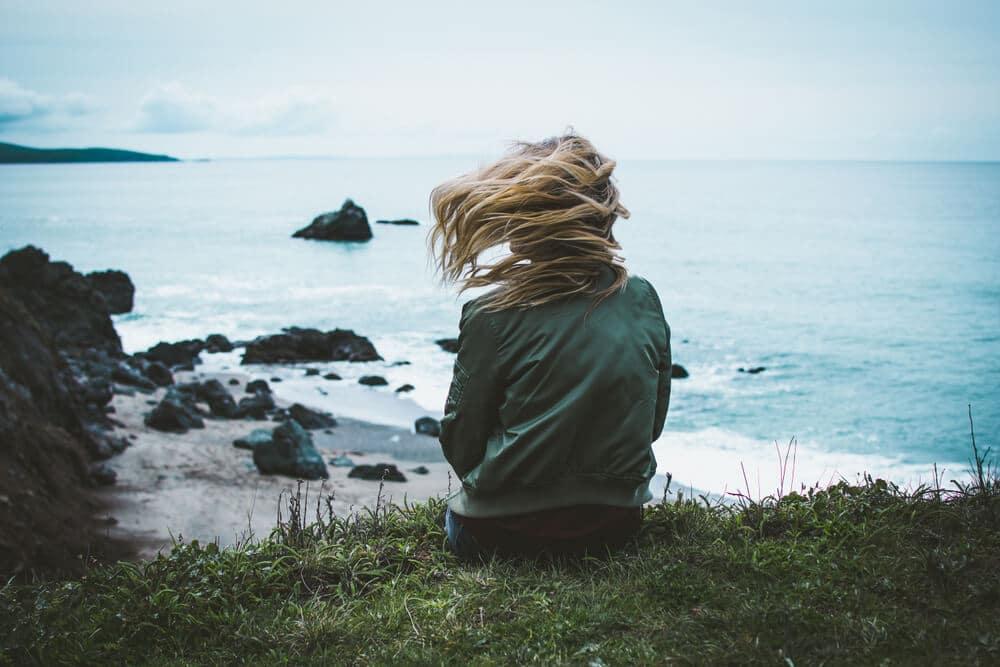 femme assise de dos sur une falaise