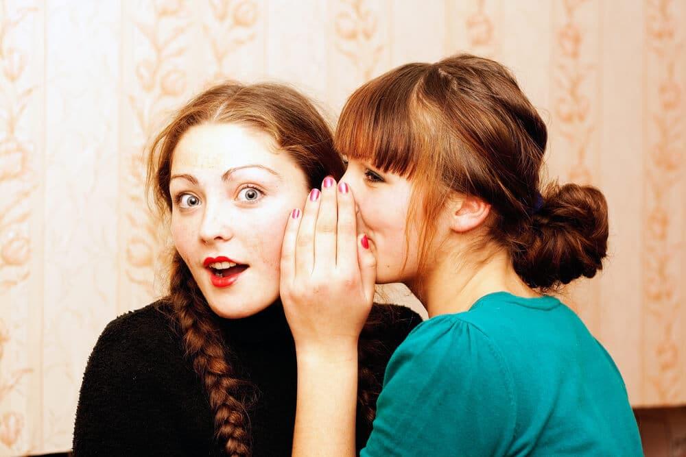 femme qui parle dans l'oreille de son amie
