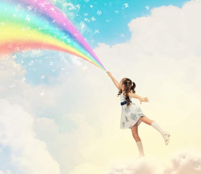enfant sur un nuage devant un arc-en-ciel