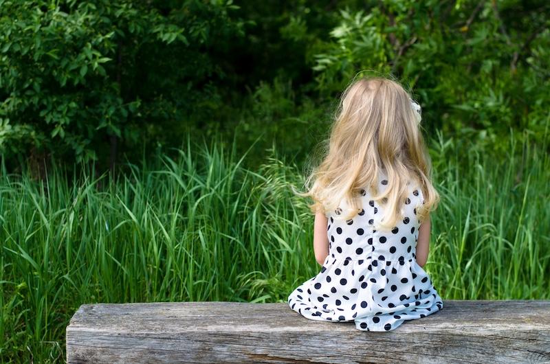 fille blonde assise sur banc