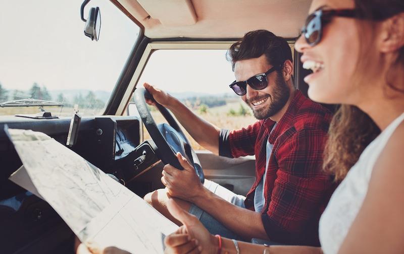 jeune couple avec une carte dans la voiture