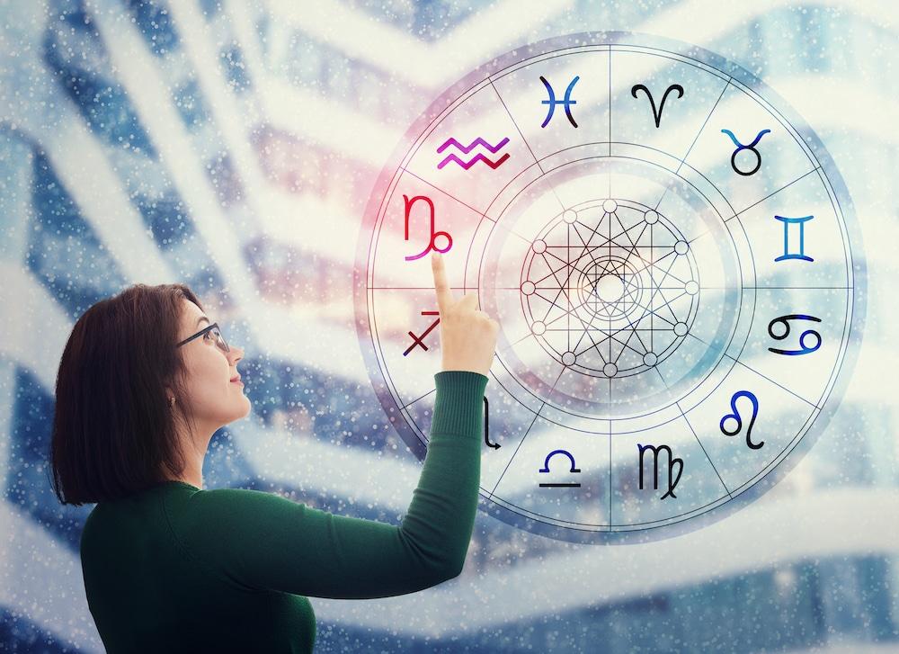 femme regardant roue astrologique
