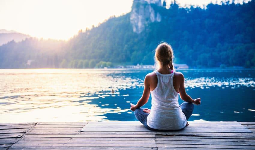 jeune femme qui fait de la meditation devant un lac