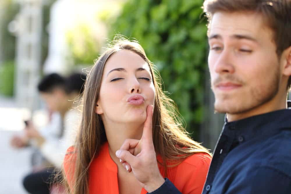 femme qui essaye d'embrasser son compagnon