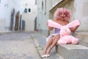 femme vetue de rose tenant une peluche