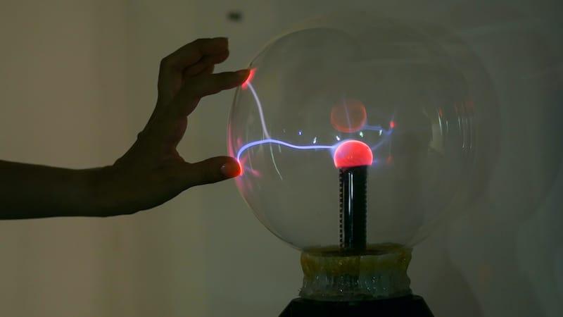 Femme qui touche une boule plasma