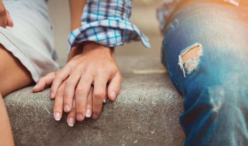 homme qui pose sa main sur celle d'une femme