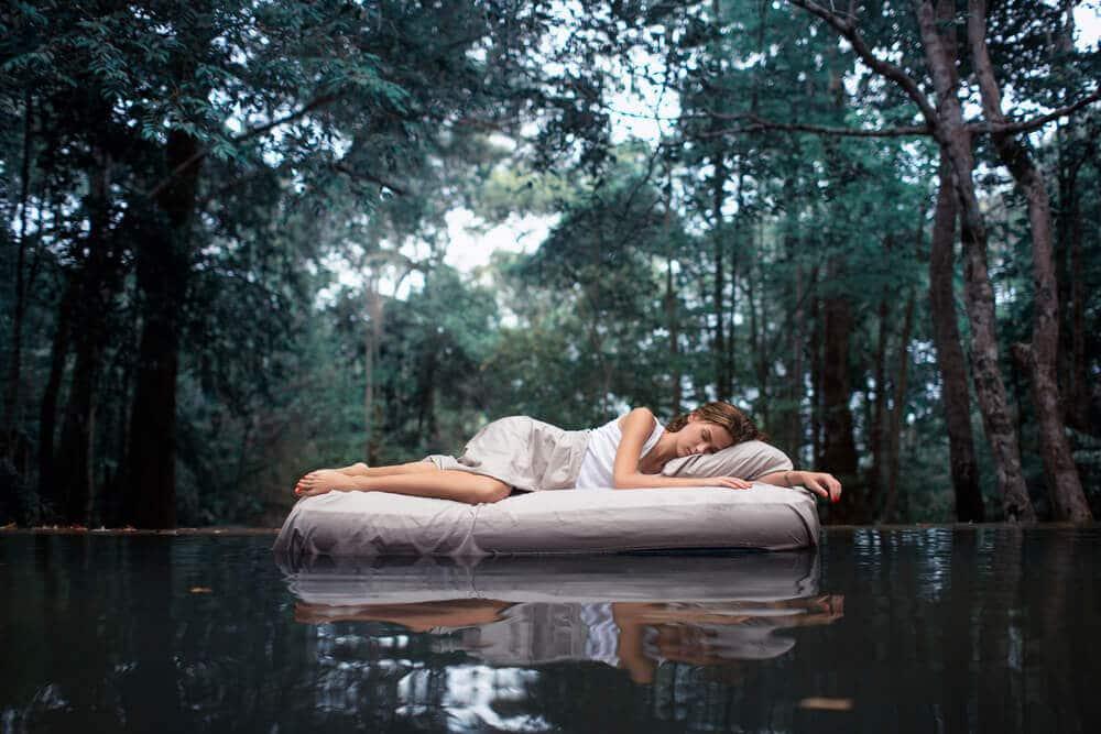 femme dormant sur un matelas au milieu d'un lac