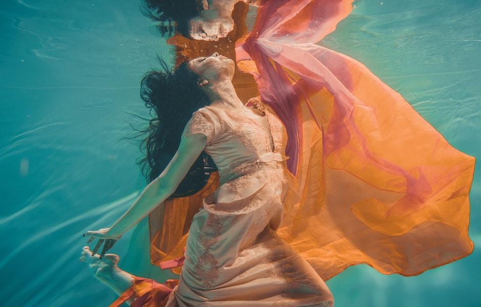 femme sous l'eau vetu d'une robe orange