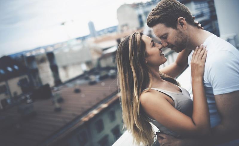 jeune couple qui s'embrasse sur un toit
