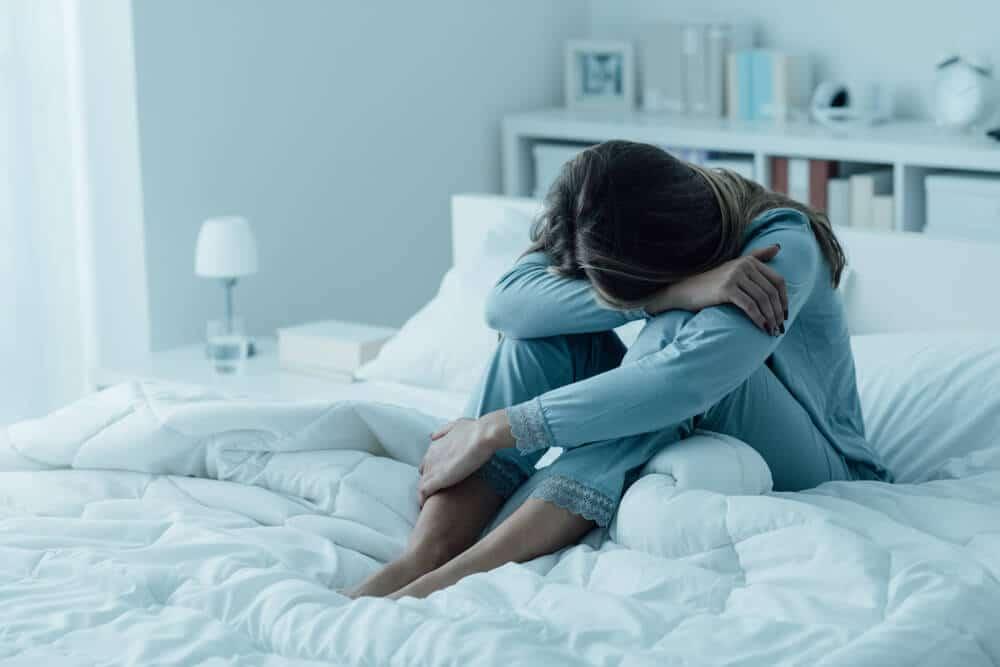 femme déprimée assise sur un lit