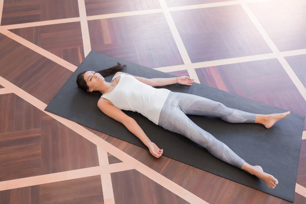 jeune femme allongé sur tapis de yoga