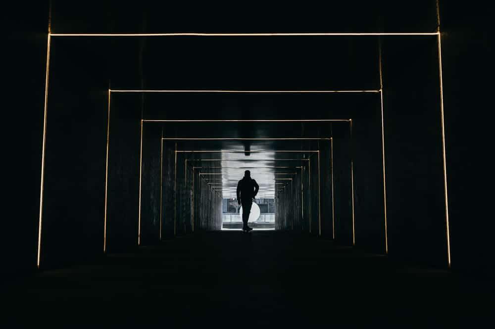 homme qui traverse un couloir obscure