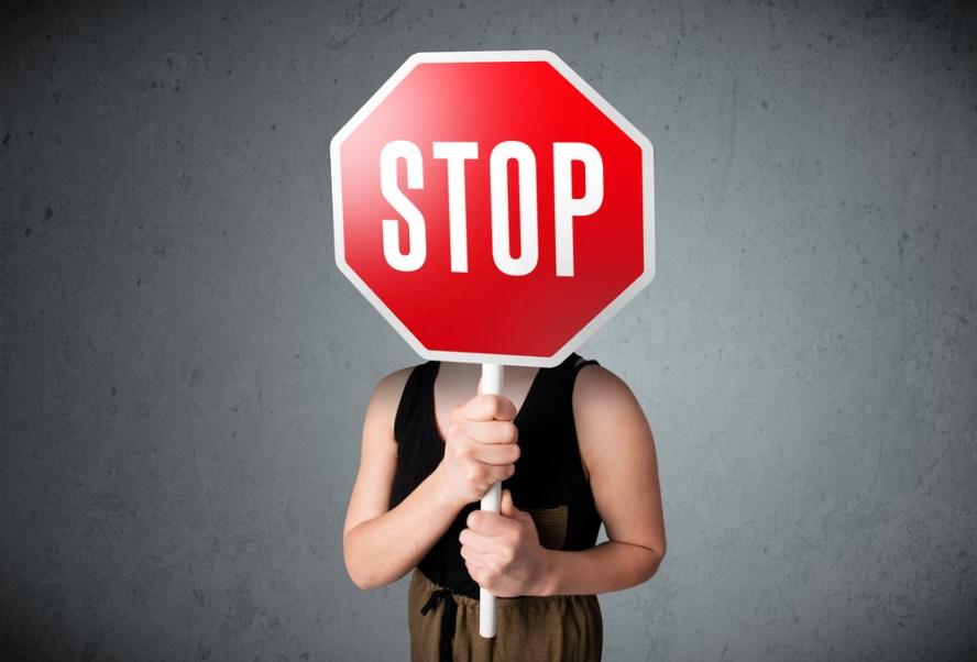 Femme tenant un panneau stop devant son visage