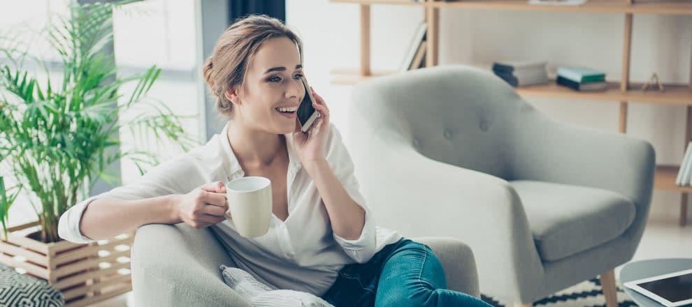 Femme dans un salon qui consulte une voyance de qualité par téléphone